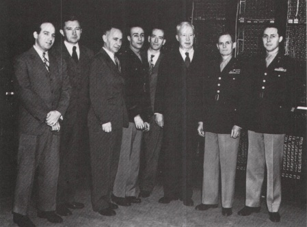 14 February 1946  De izquierda a derecha:  J. Presper Eckert, Jr.; John Grist Brainerd; Sam Feltman, chief engineer for ballistics, Army Ordnance; Herman H. Goldstine; John W. Mauchly; Harold Pender; Major General G. 1. Barnes, chief of Army Ordnance; Colonel Paul N. Gillon, chief of the Research Branch of Army Ordnance.