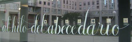 Fotografía realizada desde el exterior de Kultur Leioa. Al fondo, la Plaza José Ramón Aketxe de Leioa, en segundo plano algunas de las letras bordadas que componen la exposición.