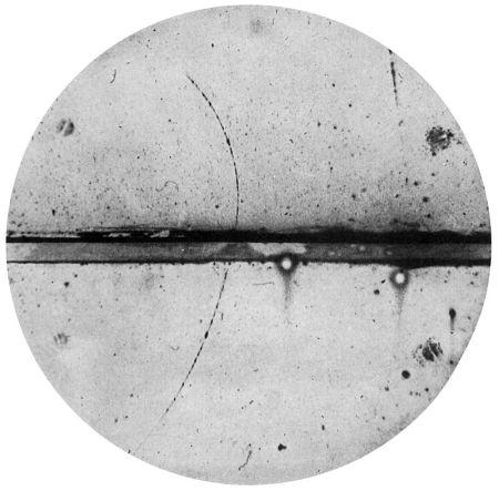 Fotografía en una cámara de niebla por C.D. Anderson, del primer positrón identificado. Una lámina de plomo de 6 mm separa la mitad superior de la cámara de la mitad inferior. El positrón debe haber venido de abajo ya que la parte superior de la pista se dobla con mayor fuerza en el campo magnético lo que indica una menor energía